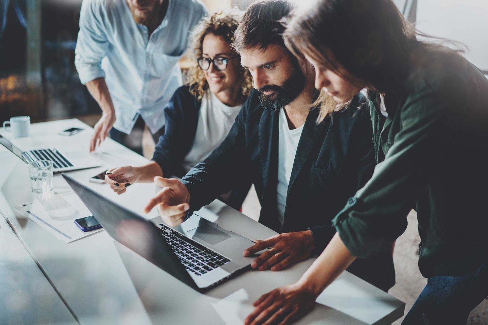 Grupp av människor som arbetar tillsammans på en laptop